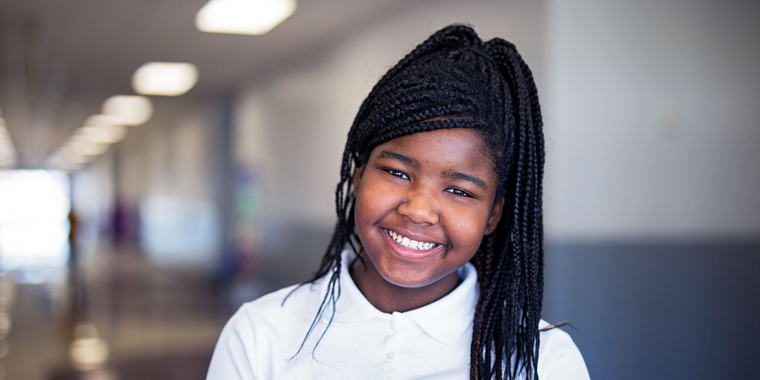 Smiling middle school student standing in hallway.