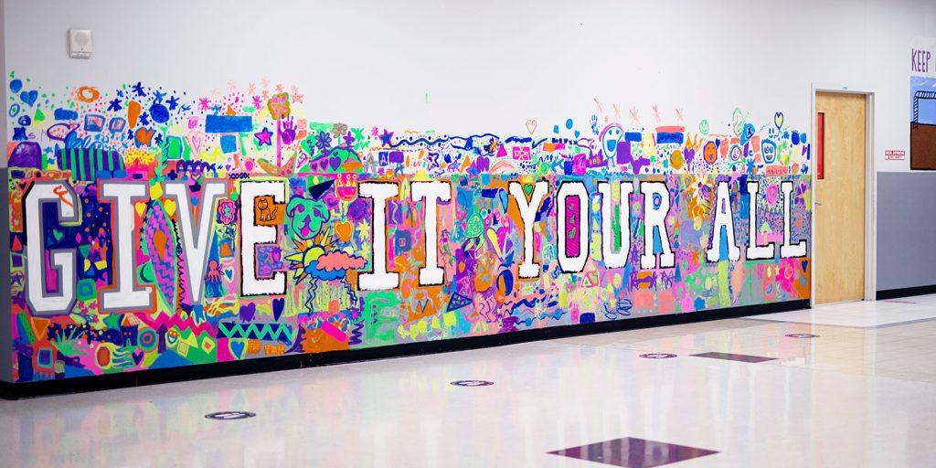 """""""Give It Your All"""" bright neon hallway mural."""