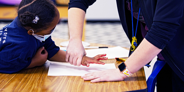 Teacher helping student with painted handprint art.