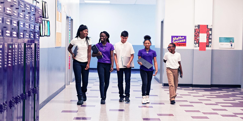 Smiling students walking down hallway.