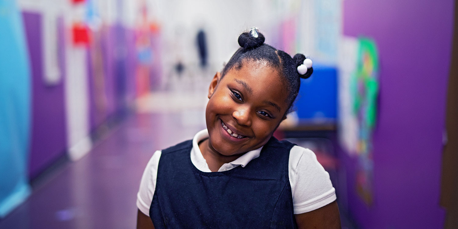 Smiling elementary student standing in hallway.